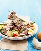 Tuna fish skewers on a salad Niçoise