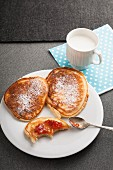 Buttermilk pancakes with icing sugar and strawberry jam on a plate with a cup of milk