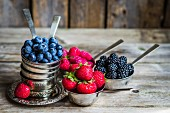 Fresh berries in silver cups on a rustic surface