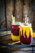 Colourful two layer mango and berry smoothies garnished with blackberries