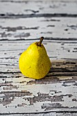 A yellow pear on a rustic wooden table