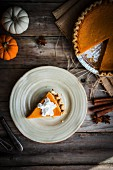 Pumpkin pie on a rustic wooden surface (seen from above)