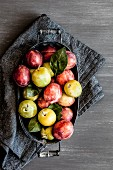 Plums with leaves in a metal bowl on a grey cloth