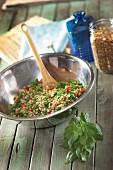 Bulgur salad with basil in a metal bowl