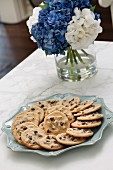 Chocolate chip cookies on a plate with a bunch of hydrangeas in the background