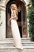 Junge Frau in langem Abendkleid auf Stufen vor antikem Eingangsportal