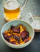 Colourful vegetable crisps (carrots, parsnips and beetroot) with salt and a beer