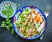 Fried noodles with salad and a fried egg (Asia)