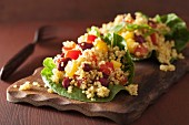 Quinoa salad with beans, peppers and tomatoes on lettuce leaves