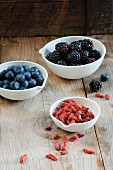 Goji berries, blackberries and blueberries in bowls on a wooden surface