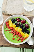 A smoothie bowl with spinach, kiwi and apple garnish with goji berries, peaches, cherries and blackberries