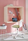 DIY-Minibüro an rosafarbener Wand - aufgehängter Holzrahmen mit integrierter Schreibtischplatte und gespannten Ablageflächen