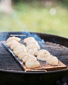Scallops being grilled on a cedar wood plank