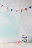 Gestapelte Papiermanschetten auf weißem Untergrund, darüber eine bunte Wimpelkette