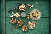 Various nuts: walnuts, hazelnuts, almonds, peanuts, cashew nuts and macadamia nuts on a wooden surface in bowls and on spoons