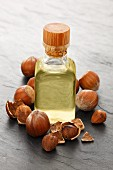 A bottle of hazelnut oil surrounded by hazelnuts