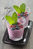 Yoghurt with blueberries, redcurrants and mint in glasses