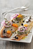 Herring fillets garnished with onion rings, carrots and juniper berries