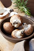 Button mushrooms in a brown bowl