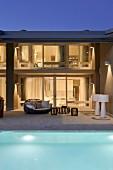 Pool und Terrasse mit Outdoormmöbeln vor zeitgenössischem Wohnhaus mit Innenbeleuchtung