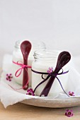 Homemade yoghurt in jars with ribbons and spoons