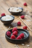 Fresh raspberries with oats and coconut on a wooden surface