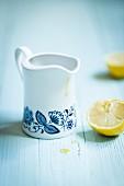 Retrokännchen mit Zitronendressing, daneben eine ausgepresste Zitronenhälfte