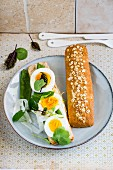 An open egg sandwich with mange tout
