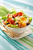 Salad with salami, half an egg, melon and olives