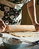 A woman rolling out shortcrust pastry