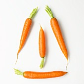 Four carrots on a white surface