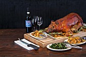 A whole roasted piglet on a serving platter with side dishes and wine
