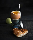 A soft-boiled egg and a piece of heart-shaped toast