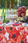 Red floral tablecloth, cake and basket of apples on table in garden