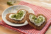 Heart-shaped slices of bread topped with quark and cress