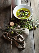 Olives and olive oil and a sprig of green olives on a rustic wooden table