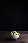 A bowl of olives on a wooden table
