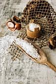 Stillleben mit Salzfässchen, Schippe mit grobem Salz, Schalotten und Fischernetz auf hellem Holz