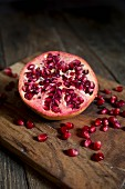 Half a pomegranate and pomegranate seeds on the wooden board
