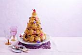 Croquembouche (franz. Torte aus Windbeuteln) mit Karamel und Essblüten