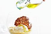Oil being pored over sorbet on fruit purée