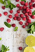 Fresh raspberries, mint and lime on a white wooden board (seen from above)
