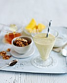 A nutrient rich milkshake, nuts, honey and mango