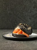A black sesame seed bagel with smoked salmon, cream cheese and bean sprouts