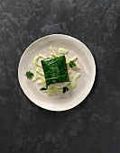 Steamed zander fillet served on a kohlrabi leaf with parsley sauce
