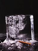 Angehackter Eisblock vor schwarzem Hintergrund
