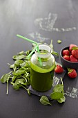 A spinach smoothie, fresh spinach leaves and strawberries