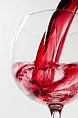 Rotwein fliesst in Weinglas