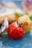 Roasted cherry tomato served with hake (close-up)