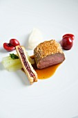 A venison medallion in a pine nut crust with French toast and red wine cherries